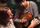 Guitar teacher teaches beginners